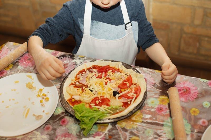 Los niños hacen la pizza Clase principal para los niños en cocinar Italia foto de archivo