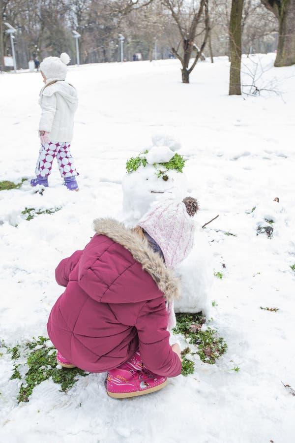 Los niños hacen un muñeco de nieve en el parque en el día de invierno imagen de archivo