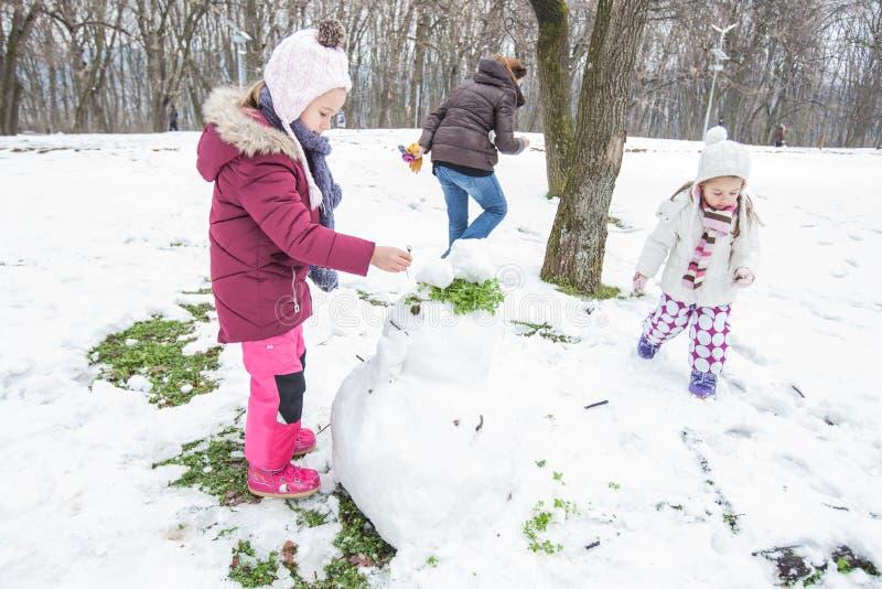 Los niños hacen un muñeco de nieve en el parque en el día de invierno fotos de archivo