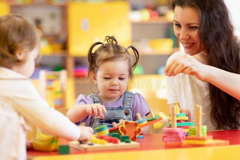 Los niños juegan con formas y rompecabezas de madera colorido en una sala de clase del montessori imagen de archivo