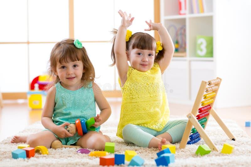 Los niños juegan con los juguetes del ábaco y del constructor, aprendiendo temprano fotos de archivo libres de regalías