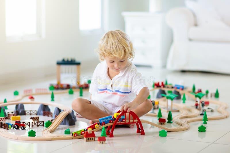 Los niños juegan el ferrocarril de madera Ni?o con el tren del juguete imágenes de archivo libres de regalías