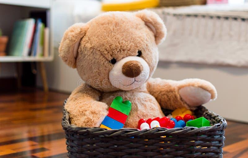 Los niños juegan el fondo con el oso de peluche y los ladrillos coloridos fotos de archivo
