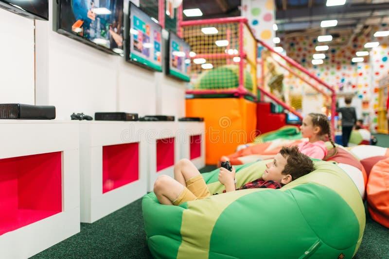 Los niños juegan en una consola de los juegos, niñez feliz imagenes de archivo