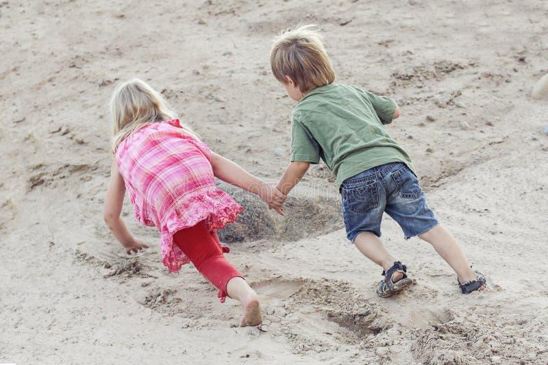 Los niños juegan juntos y superan dificultades Concepto de la ayuda al aire libre foto de archivo