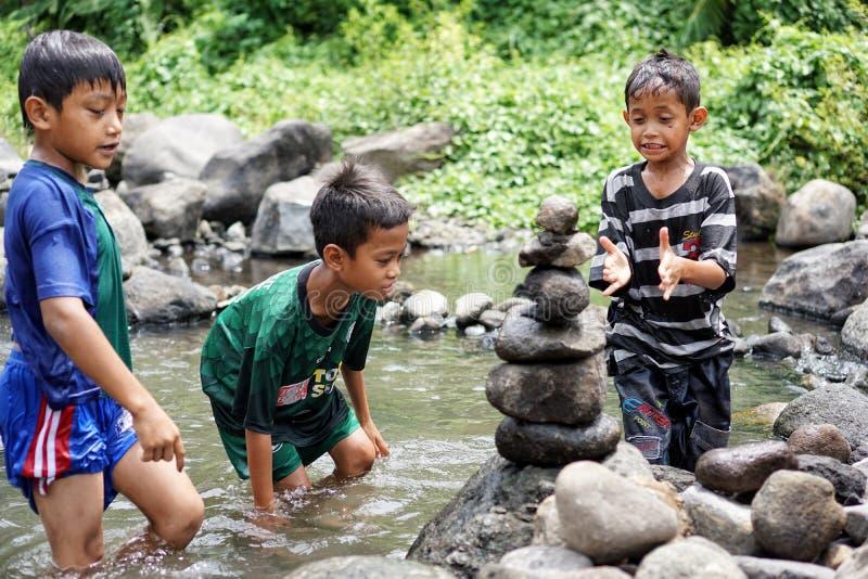Los niños juegan la roca que equilibra en los bancos del río imagen de archivo libre de regalías