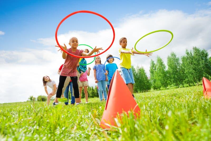 Los niños lanzan aros coloridos en conos mientras que compiten foto de archivo