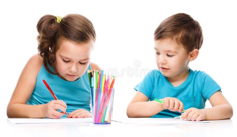 Los niños lindos están dibujando en el Libro Blanco imagen de archivo
