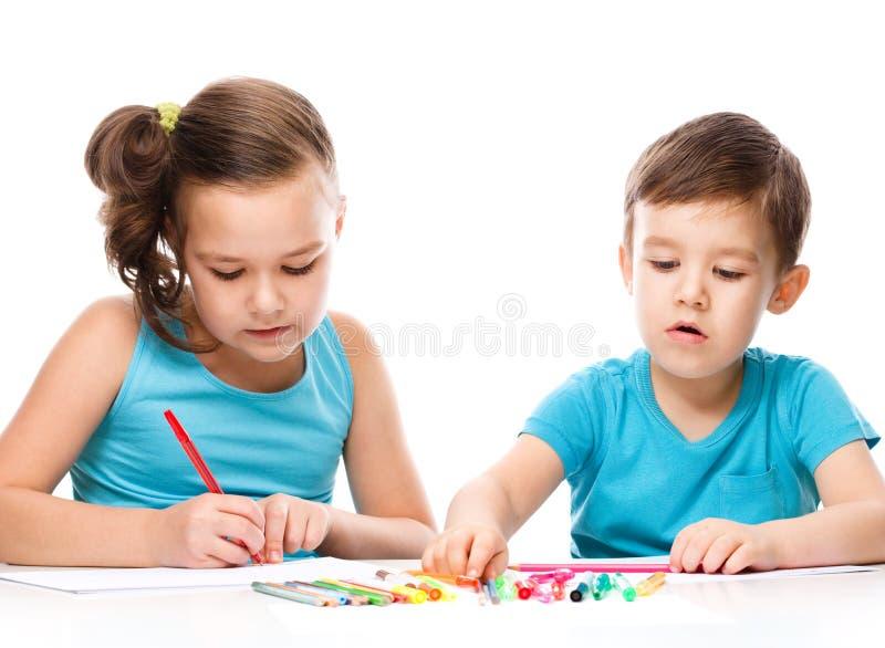 Los niños lindos están dibujando en el Libro Blanco fotos de archivo