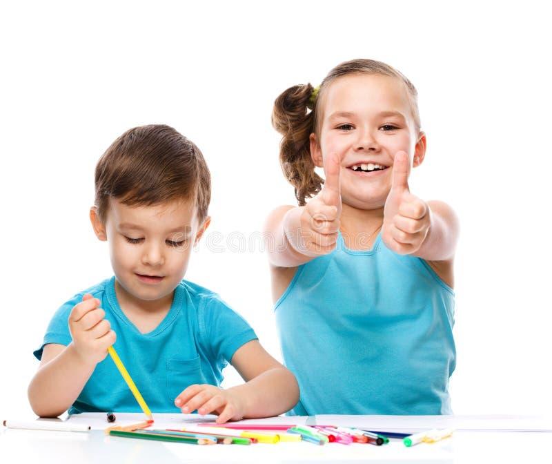 Los niños lindos están dibujando en el Libro Blanco foto de archivo libre de regalías