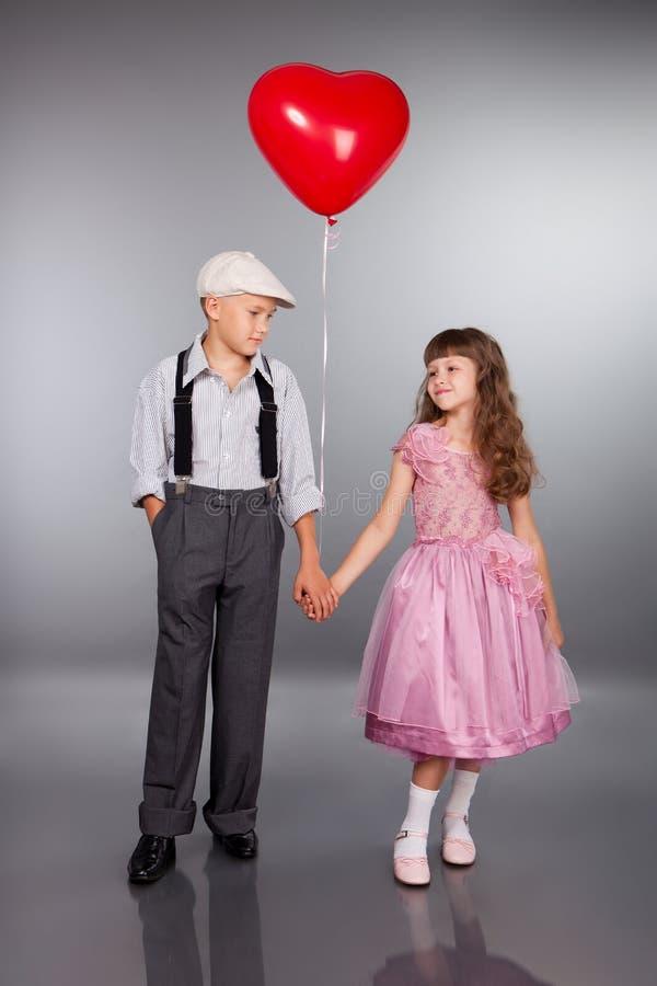 Los niños lindos recorren con un globo rojo imagen de archivo libre de regalías