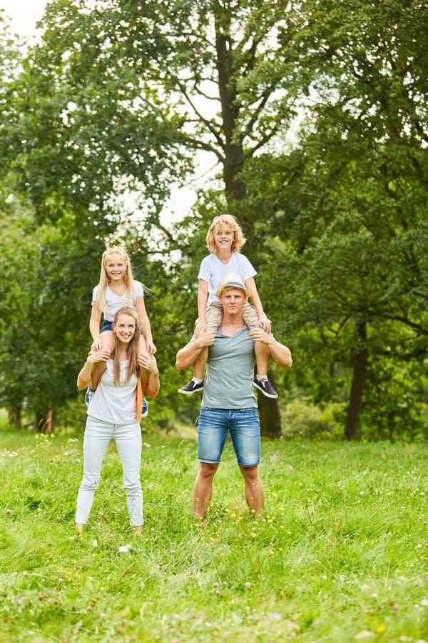 Los niños montan en la parte de atrás de sus padres fotografía de archivo