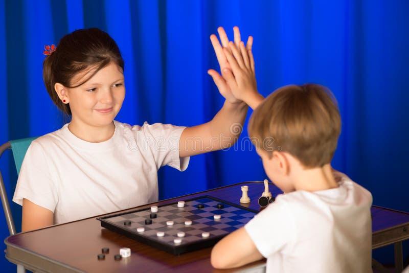 Los niños muchacho y muchacha que jugaban a un juego de mesa llamaron a Checkers imagen de archivo libre de regalías