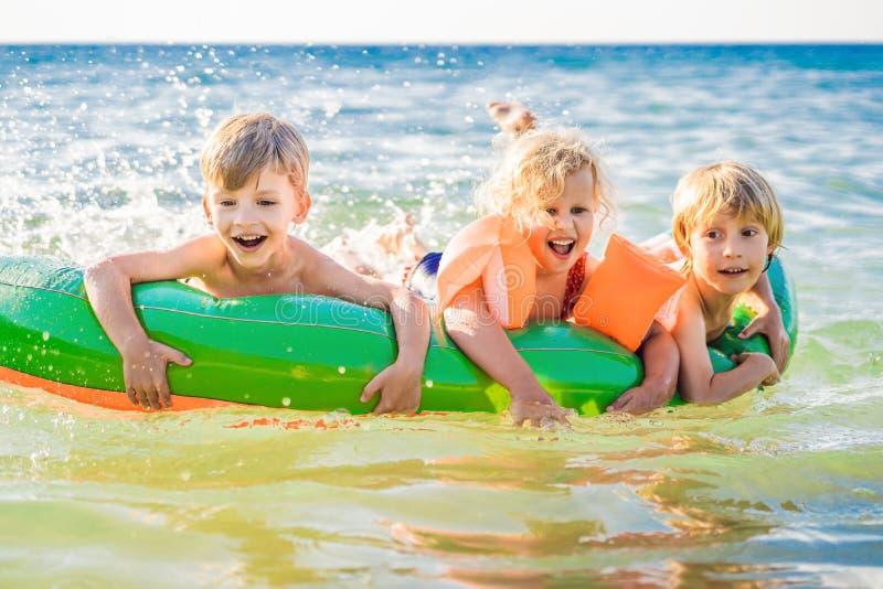 Los niños nadan en el mar en un colchón inflable y divertirse imagenes de archivo