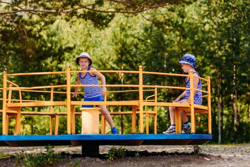 Los niños pequeños en sombreros y camisetas montan un carrusel grande del hierro en el parque fotografía de archivo