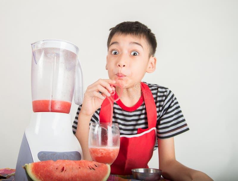 Los niños pequeños mezclan el jugo del melone del agua usando hogar de la licuadora imagen de archivo libre de regalías