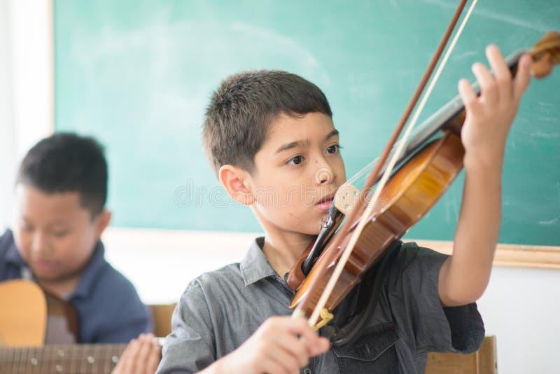 Los niños pequeños tocan y practican el violín en la clase de música fotografía de archivo libre de regalías