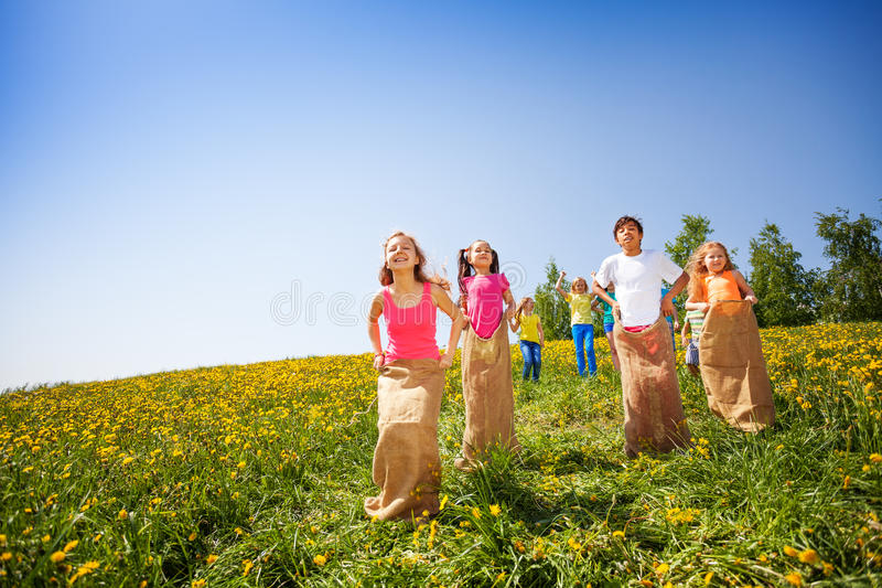 Los niños positivos saltan en sacos y jugar foto de archivo