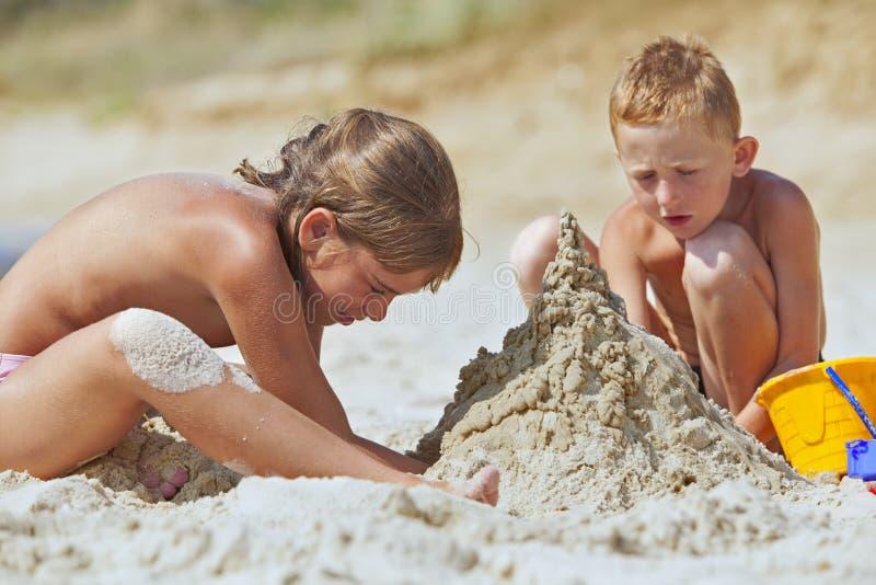 Los niños que construyen la arena se escudan en la playa fotografía de archivo