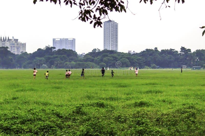 Los niños que corren en el parque de primavera colocan en ropa casual imagen de archivo libre de regalías