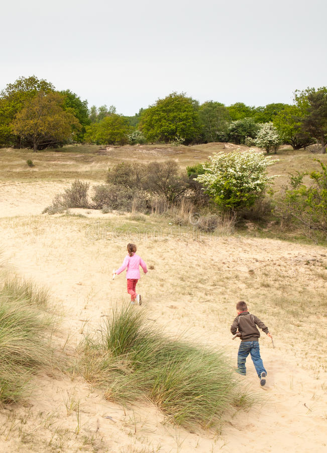 Los niños que corren en una duna ajardinan foto de archivo