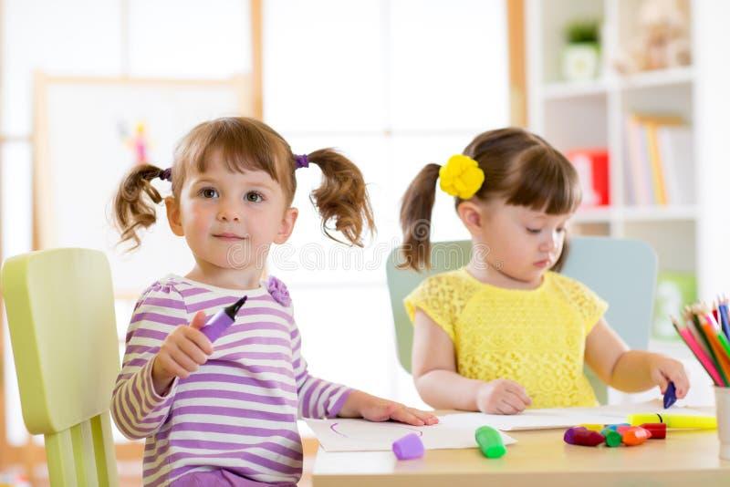 Los niños que dibujan adentro kindergaten Los niños pintan en cuarto de niños Preescolar con la pluma en casa Niño creativo imagenes de archivo