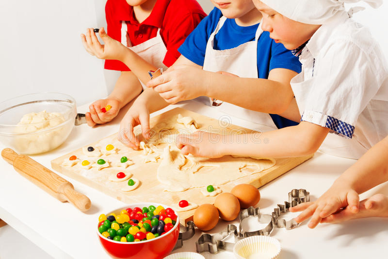 Los niños que hacían el caramelo llenaron las galletas en el escritorio de madera imagen de archivo libre de regalías
