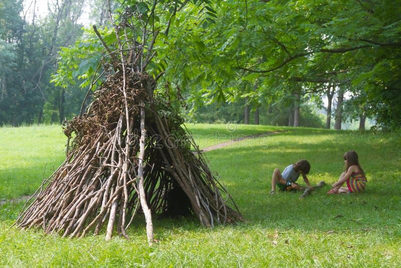 Los niños que juegan al lado del palillo de madera contienen parecerse choza india, imagen de archivo libre de regalías