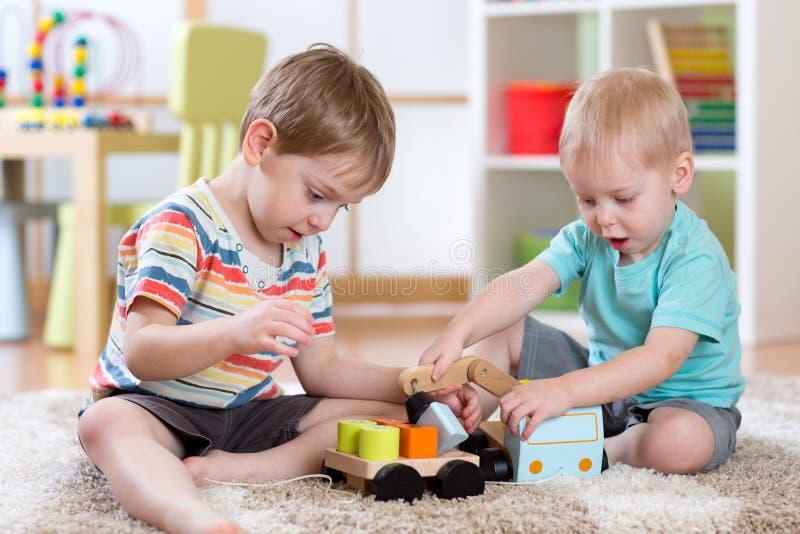 Los niños que juegan el coche juegan en cuarto de niños o guardería fotos de archivo