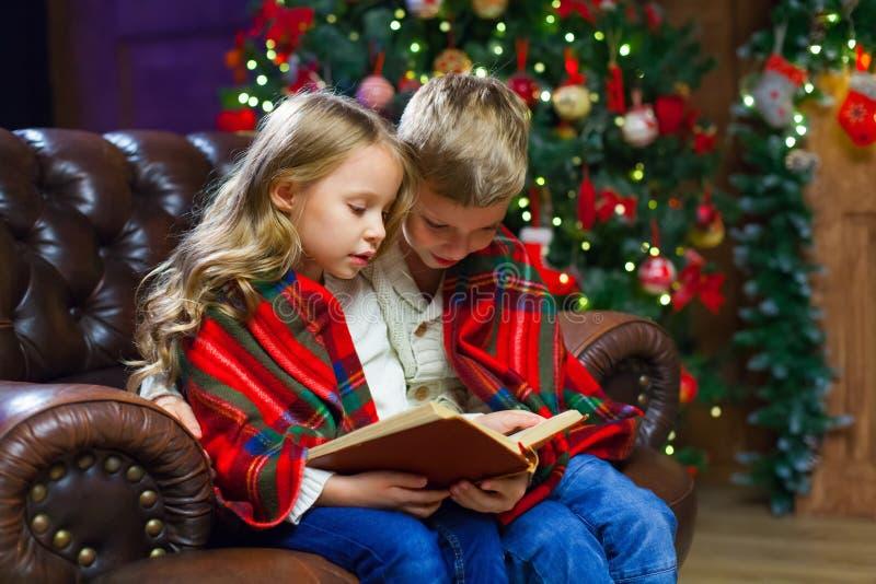 Los niños que leen un interés reservan sentarse en la cama contra foto de archivo