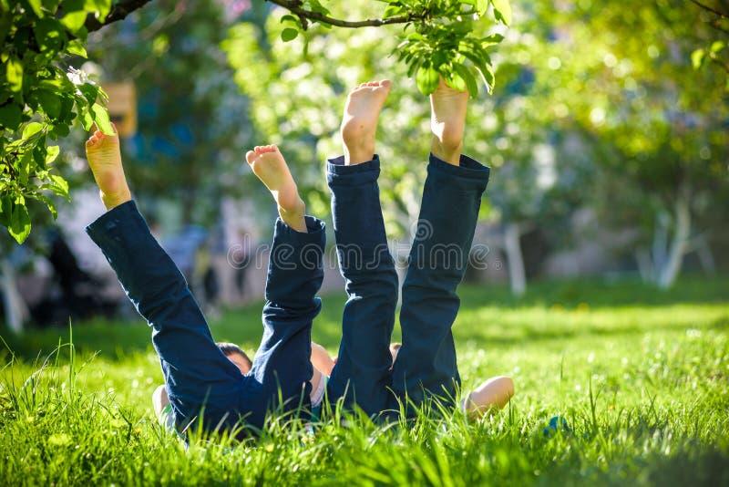 Los niños que mentían en hierba verde en parque en un día de verano con sus piernas levantaron hasta el cielo imagenes de archivo