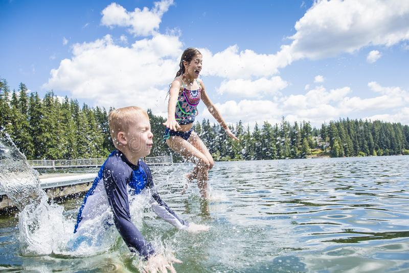 Los niños que saltan del muelle en un lago hermoso de la montaña Divertirse en vacaciones de verano foto de archivo
