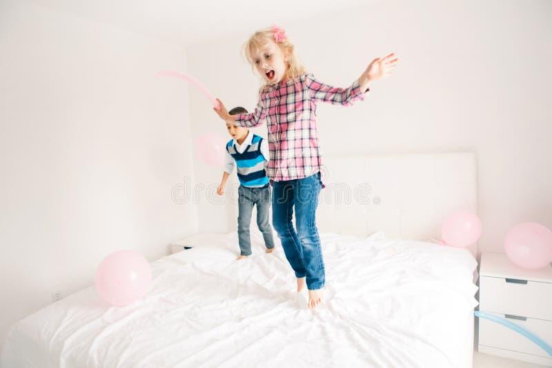Los niños que saltan en cama en dormitorio y jugar fotos de archivo