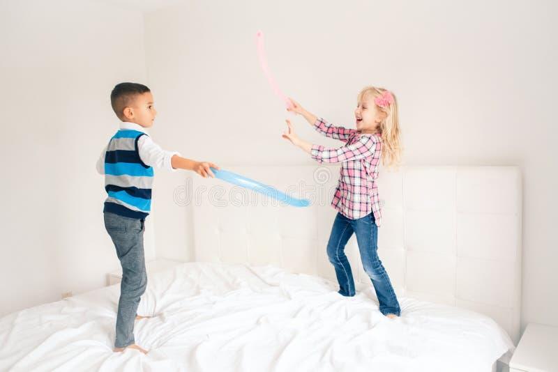 Los niños que saltan en cama en dormitorio y jugar imagenes de archivo
