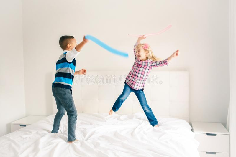 Los niños que saltan en cama en dormitorio y jugar foto de archivo libre de regalías
