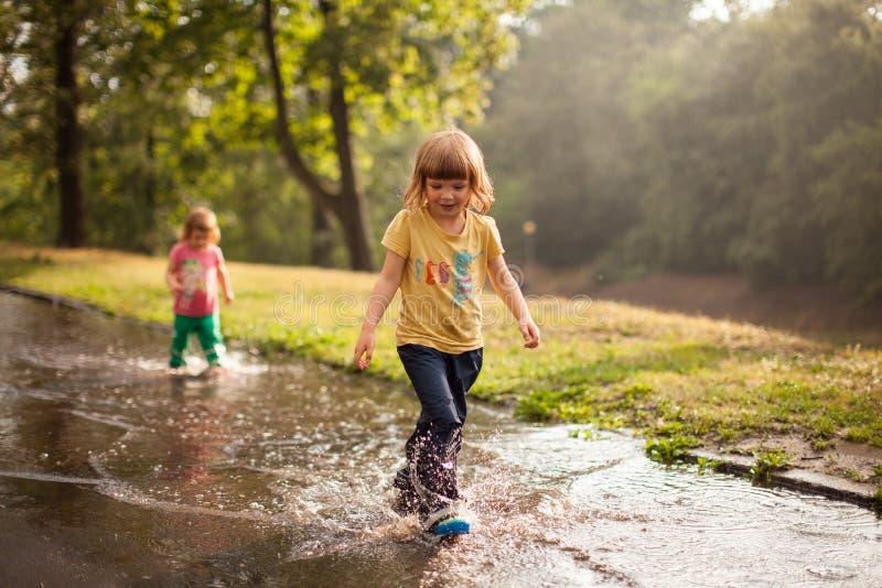 Los niños que saltan en charco del agua fotos de archivo libres de regalías
