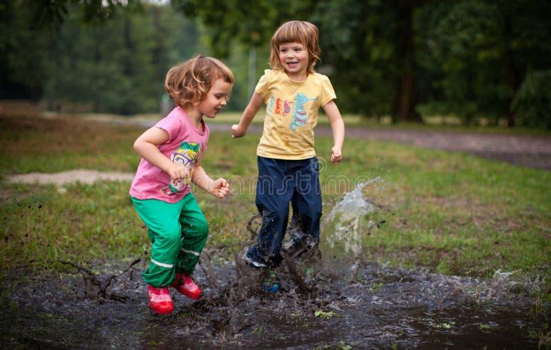 Los niños que saltan en charco del agua fotos de archivo