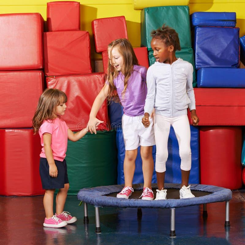 Los niños que saltan en el trampolín en gimnasio imagen de archivo