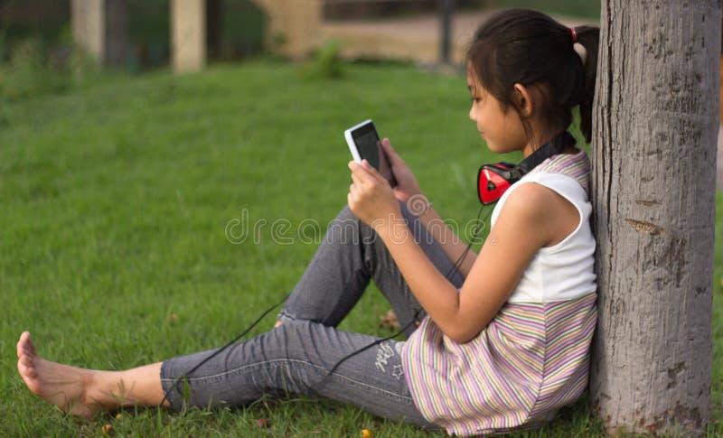 Los niños que se sientan en el césped y disfrutan del juego fotos de archivo