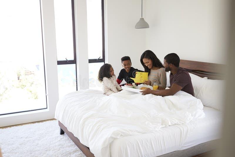 Los niños que traen a padres desayunan en cama para celebrar día o cumpleaños de madres imagen de archivo