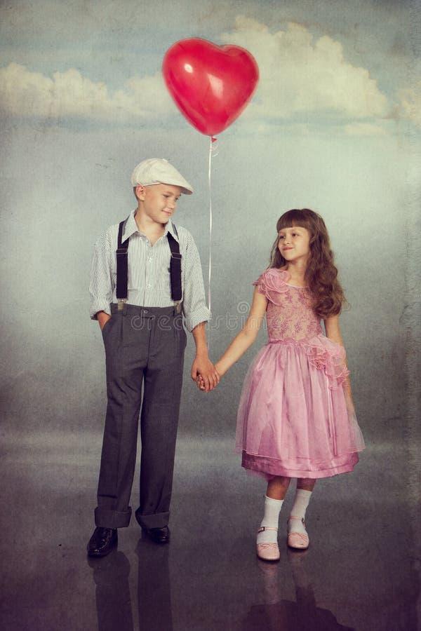 Los niños recorren con un globo fotos de archivo