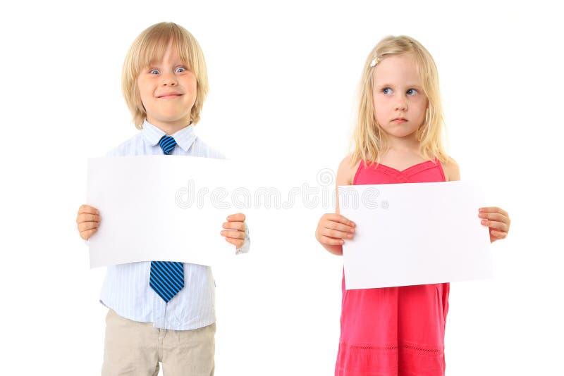 Los niños rubios jovenes que llevan a cabo una muestra en blanco suben imagen de archivo