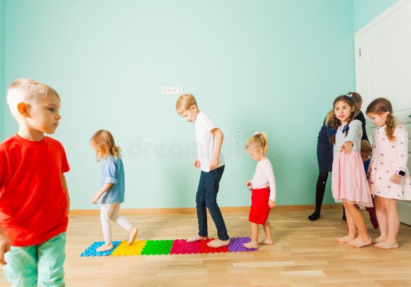Los niños se colocan descalzo en fila entre las esteras del masaje imagen de archivo libre de regalías