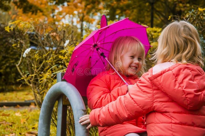 los niños se divierten debajo de un paraguas, en la tarde del otoño fotos de archivo