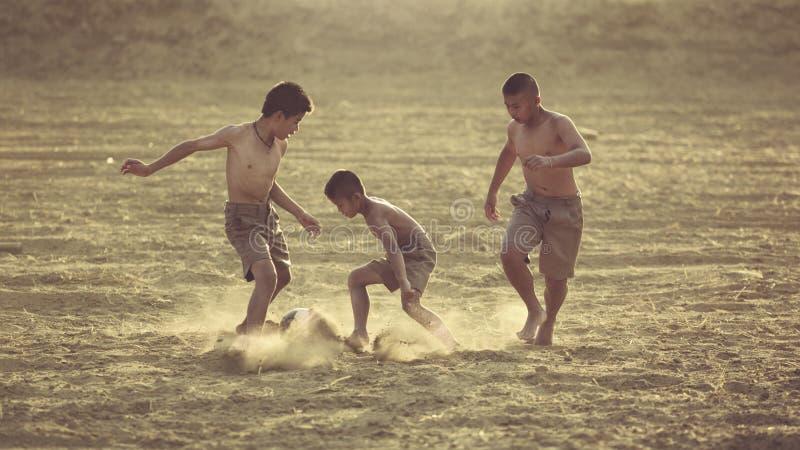 Los niños se están divirtiendo que juega a fútbol en el campo imagen de archivo libre de regalías