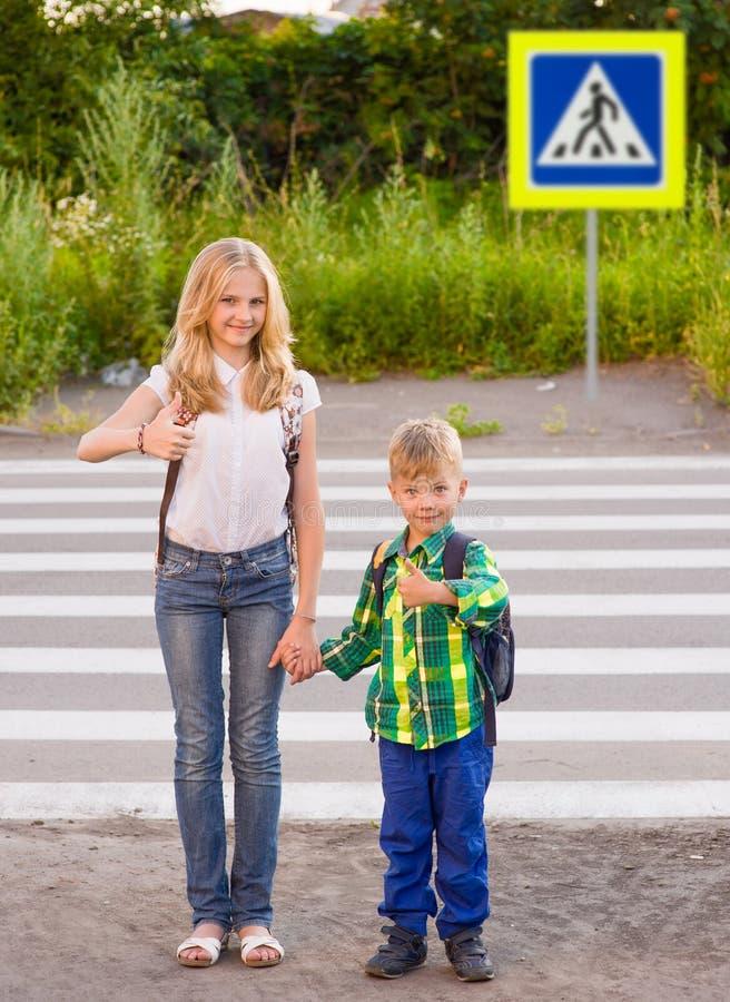Los niños se levantan cerca de un paso de peatones y de los pulgares de la demostración imagen de archivo libre de regalías