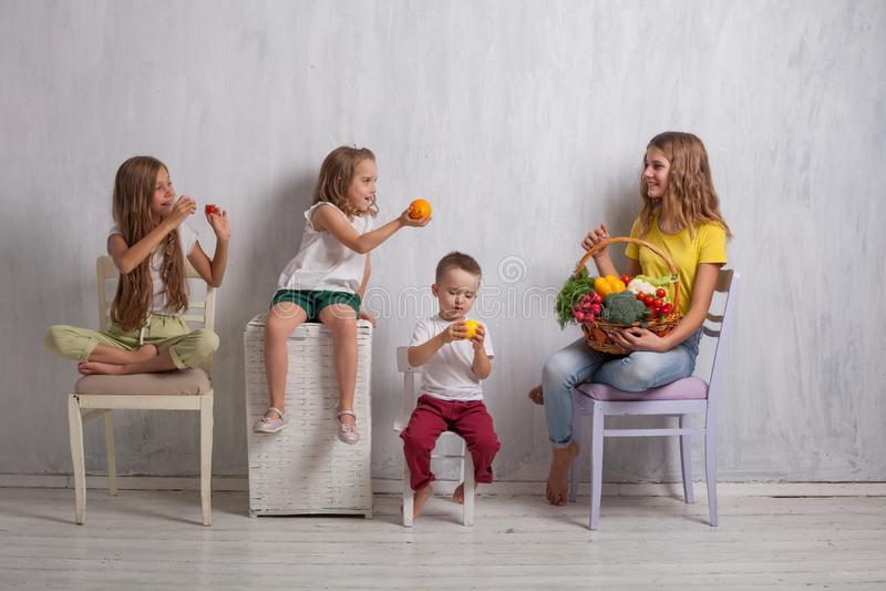 Los niños se sientan con la fruta sana de la consumición de las verduras frescas foto de archivo libre de regalías