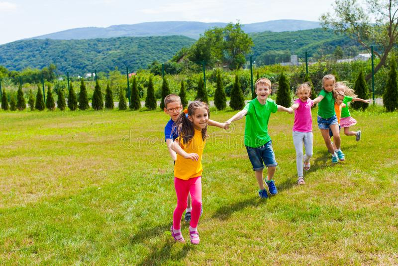 Los niños siguen a la chica, feliz momento con sus amigos imagen de archivo
