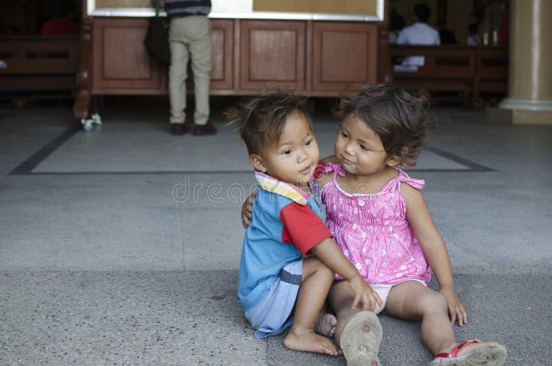 Los niños sin hogar muchacho y muchacha del ` s del mendigo, asentados, toman el cuidado de uno a en la yarda de la iglesia fotografía de archivo