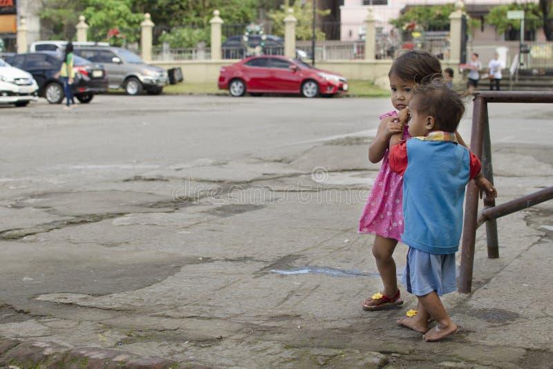 Los niños sin hogar muchacho y muchacha del ` s del mendigo, caminando, toman el cuidado de uno a en la yarda de la iglesia fotografía de archivo libre de regalías